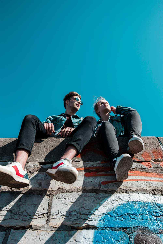 Teens sitting on a brick wall