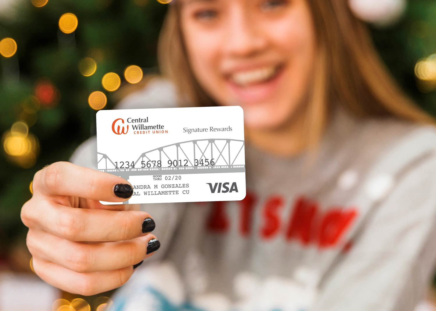 Woman showing off her Central Willamette Credit Union Credit Card