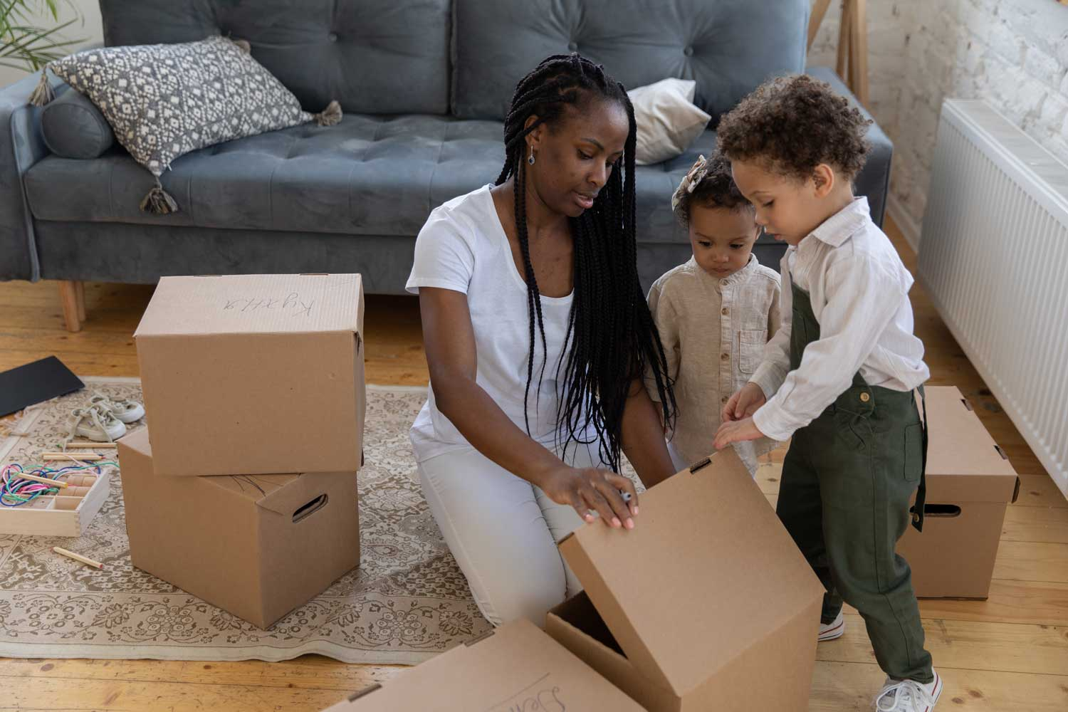 Woman with kids on their new home unpacking boxes