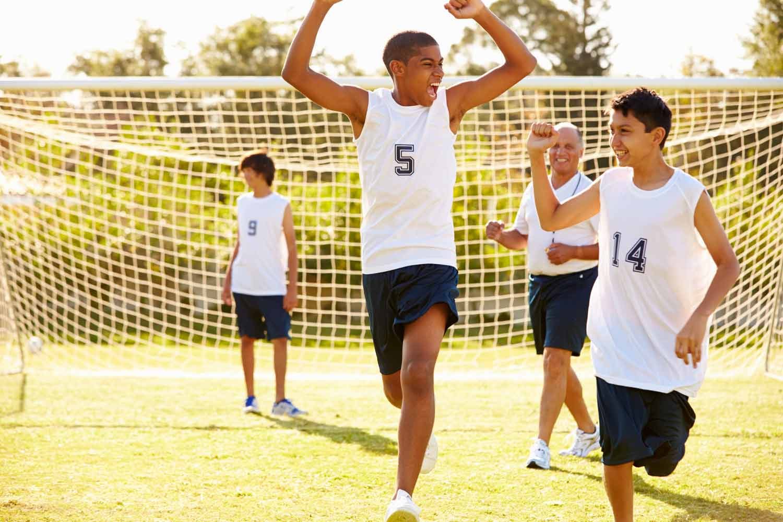 Teen scores a goal playing soccer