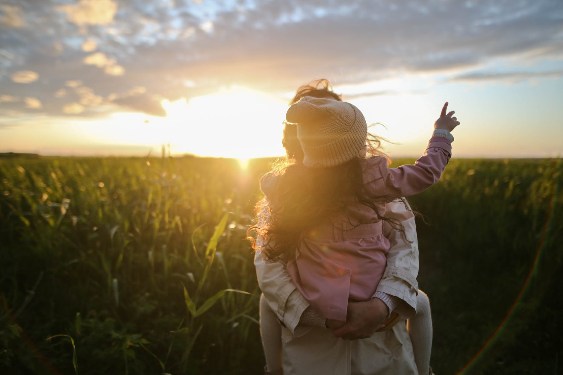 Mother holding child on a corn field looking at the sunset