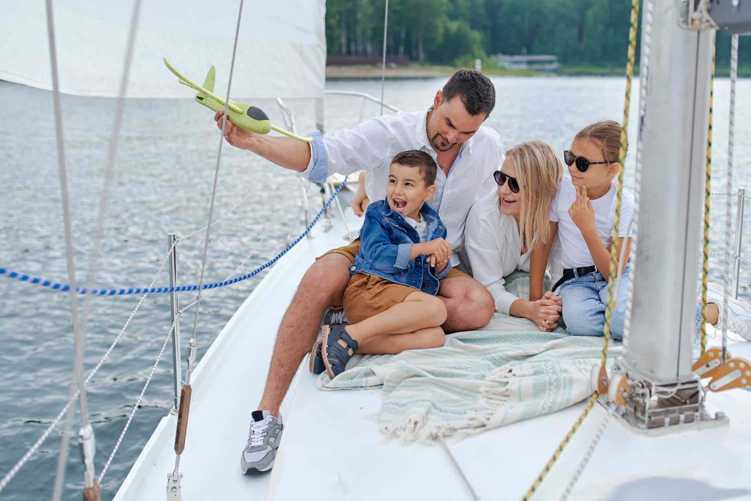 Family on a boat. Father playing with a toy airplane with son, mother and daughter wearing sun glasses